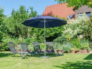 Der Garten unserer Ferienwohnung mit großzügiger Liegewiese, Sonnenschirm und Sonnenliegen.